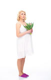 A young blond pregnant woman holding flowers Stock Photography
