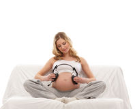 A young blond pregnant woman holding headphones Stock Photo