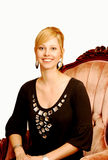 Young blond pretty girl. An blond young lady sitting in an old arm chair in a brown top Stock Photo