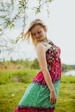 Young blond  pretty lady in green and red sundress Stock Photography