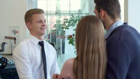 Salesman shakes hands with customer at the car dealership. Young blond salesman shaking hands with customer at the car dealership. Caucasian sales manager in stock photography