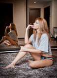 Young blond sensual woman sitting on the floor thinking. Beautiful young girl with comfortable clothes relaxing on the carpet Stock Photography