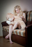 Young blond sensual woman sitting on sofa relaxing with a huge teddy bear Royalty Free Stock Photos