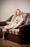 Young blond sensual woman sitting on sofa relaxing with a huge teddy bear. Beautiful girl with comfortable clothes relaxing on the couch with a toy. Attractive Royalty Free Stock Image