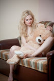 Young blond sensual woman sitting on sofa relaxing with a huge teddy bear Stock Images