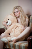Young blond sensual woman sitting on sofa relaxing with a huge teddy bear. Beautiful girl with comfortable clothes relaxing on the couch with a toy. Attractive Royalty Free Stock Photography