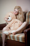 Young blond sensual woman sitting on sofa relaxing with a huge teddy bear. Beautiful girl with comfortable clothes relaxing on the couch with a toy. Attractive Stock Photo