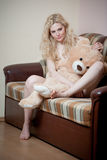 Young blond sensual woman sitting on sofa relaxing with a huge teddy bear. Beautiful girl with comfortable clothes relaxing on the couch with a toy. Attractive Stock Photography