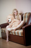 Young blond sensual woman sitting on sofa relaxing with a huge teddy bear Royalty Free Stock Photo