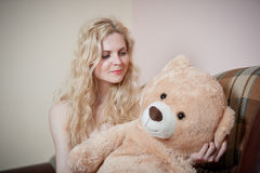 Young blond sensual woman sitting on sofa relaxing with a huge teddy bear. Beautiful girl with comfortable clothes relaxing on the couch with a toy. Attractive Stock Photos