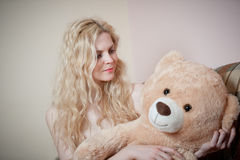 Young blond sensual woman sitting on sofa relaxing with a huge teddy bear. Beautiful girl with comfortable clothes relaxing on the couch with a toy. Attractive Royalty Free Stock Photos