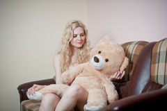 Young blond sensual woman sitting on sofa relaxing with a huge teddy bear. Beautiful girl with comfortable clothes relaxing on the couch with a toy. Attractive Stock Images