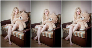 Young blond sensual woman sitting on sofa relaxing with a huge teddy bear. Beautiful girl with comfortable clothes relaxing on the couch with a toy. Attractive Royalty Free Stock Photo