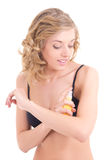 Young blond spraying lotion on her shoulder Stock Image