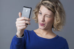 Young blond taking selfie and sticking out her tongue Royalty Free Stock Image