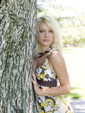 Young blond teen girl outdoors next to tree. Outdoor portrait of young blond teen in dress Royalty Free Stock Images
