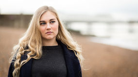 Young Blond Teenage Girl Thinking On The Beach Stock Photography