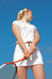 Young blond  tennis-player in white sportwear outd. Girl in white with tennis racket on background of sky Royalty Free Stock Photos