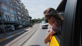 Young blond tourist woman riding in a taxi, and leaning out of window looks at city. Young blond tourist woman riding in a taxi in the back seat, and leaning out stock video