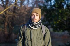 Young blond white man with a beard wearing a scarf, hat and backpack royalty free stock photos