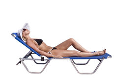 Young blond white woman on sunbed. Young blond white woman lying on blue sunbed isolated over white background Stock Photos