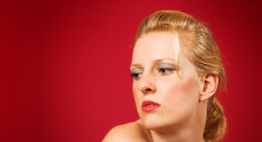 Young blond woman. Portrait of attractive young blond woman with glamorous hairstyle; red background with copy space Stock Image