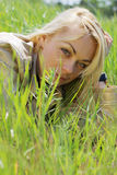 Young blond woman. Lying in green grass Royalty Free Stock Photos
