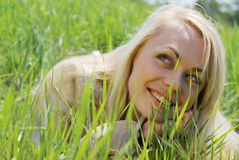 Young blond woman. Lying in green grass Stock Images