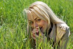 Young blond woman. Lying in green grass Royalty Free Stock Images
