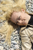 Young blond woman. With scattered hair lying on pebble Royalty Free Stock Image