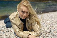 Young blond woman. Lying on pebble on sea background Royalty Free Stock Images