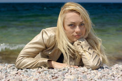 Young blond woman. Lying on pebble on sea background Stock Photos