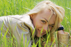 Young blond woman. Lying in green grass Royalty Free Stock Photo