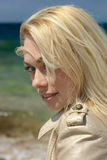 Young blond woman. Close-up on sea background Royalty Free Stock Images