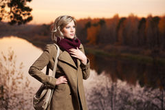Young fashion woman in beige coat with handbag walking outdoor Royalty Free Stock Photo