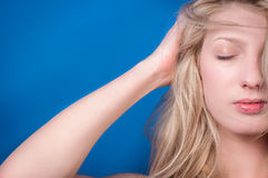 Young blond woman against blue wall Stock Photos