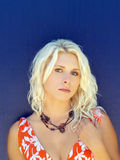 Young blond woman against blue wall melancholy Royalty Free Stock Photography