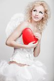 Young blond woman in angel costume. Holding heart Royalty Free Stock Images