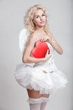 Young blond woman in angel costume. Holding heart Royalty Free Stock Photos