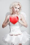 Young blond woman in angel costume. Holding heart Stock Photos