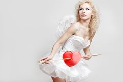 Young blond woman in angel costume. Holding heart arrow Stock Images