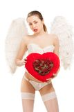 Young blond woman in angel costume holding heart. This image has attached release Royalty Free Stock Photos