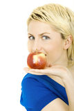Young blond woman with an apple Stock Photography