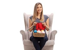 Young blond woman in an armchair knitting and looking at the camera royalty free stock photos