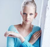 Young blond woman in azure sweater. Portrait of young blond woman in azure sweater. Crossed arms Stock Photo