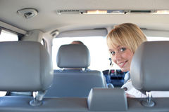 Young blond woman on a backseat of a car Stock Photo