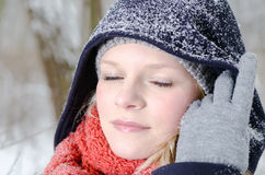 Young blond woman with beanie and scarf winter wood portrait Stock Image