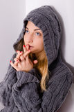 Young blond woman beautiful girl in hood praying. Beautiful young woman blond girl in hood praying & looking up Stock Photography