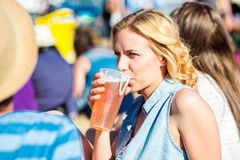 Young blond woman with beer at summer music festival Stock Images