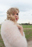 Young blond woman in a beige dress and a short pink fur coat on the countryside road Stock Image